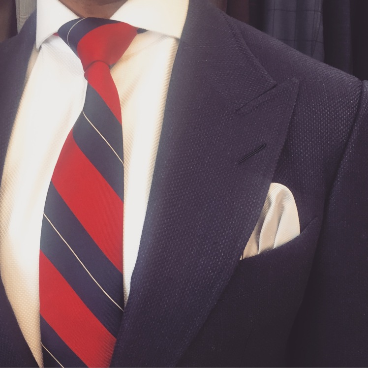 Navy suit with red and navy striped tie